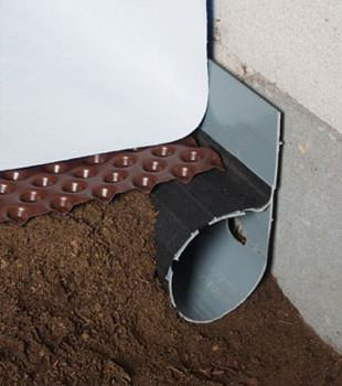 Closeup of a crawl space drainage system installed in East Longmeadow
