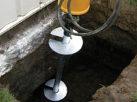 Installing a helical pier system in the earth around a foundation in Pittsfield